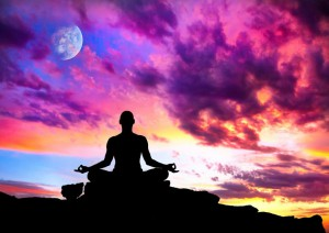 Yoga meditation in lotus pose by man silhouette with moon and purple dramatic sunset sky background.