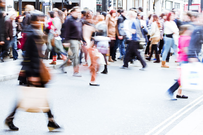 shopping crowd crossing the city street in motion blur