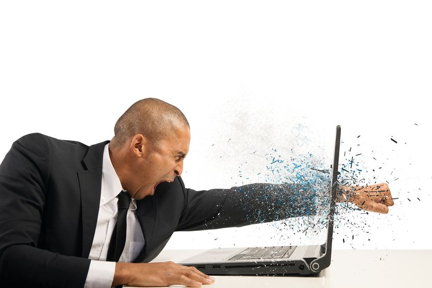 Businessman punches through laptop screen