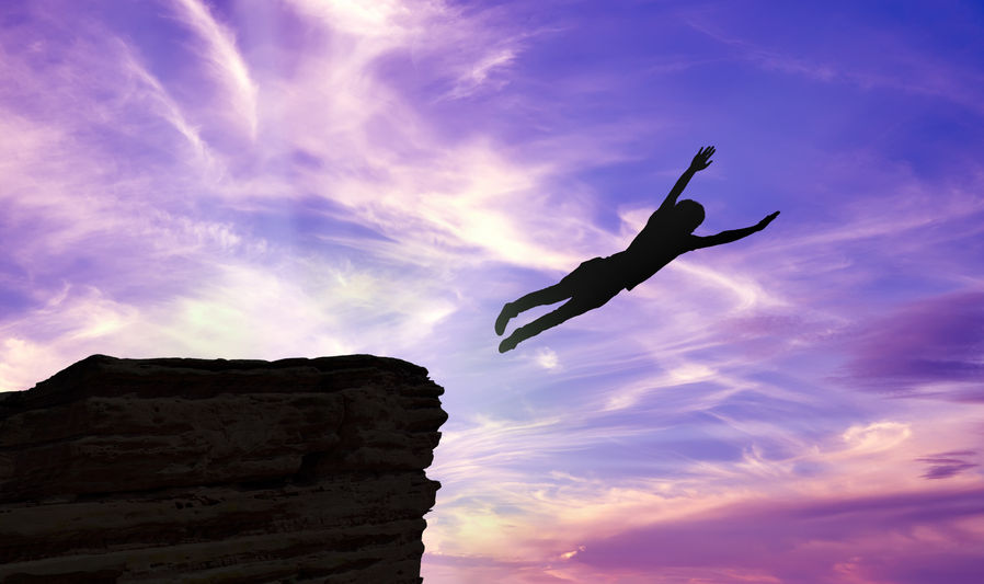 Silhouette of a man jumping off a cliff over purple background