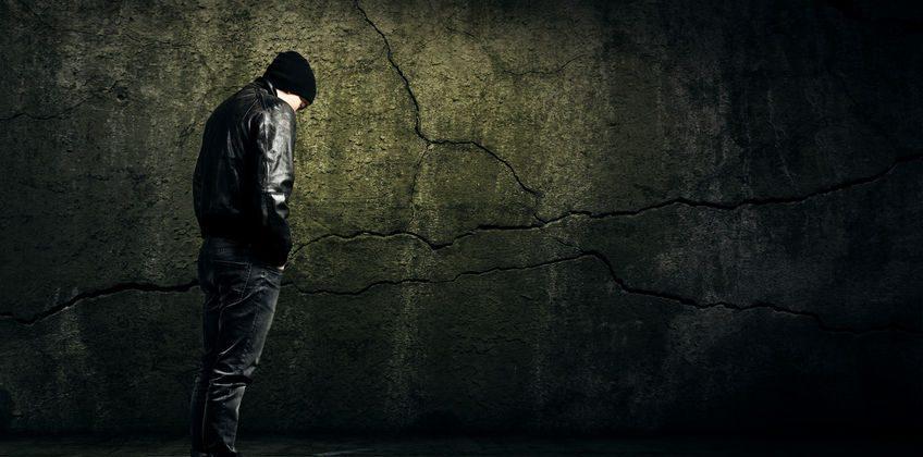 Man Alone against a wall, a grim dark tone