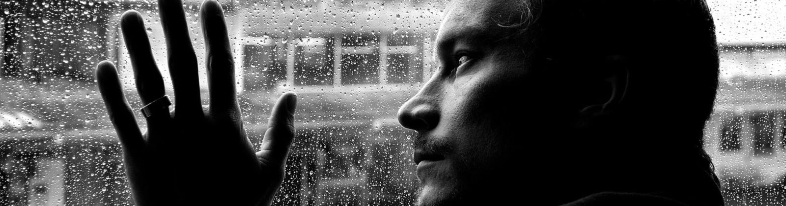 Safe but depressed, man looking out of a window