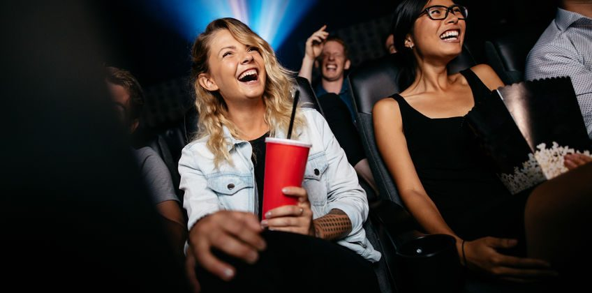 Young people laughing while watching film in movie theatre