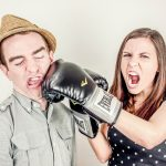 Woman punching man with boxer gloves